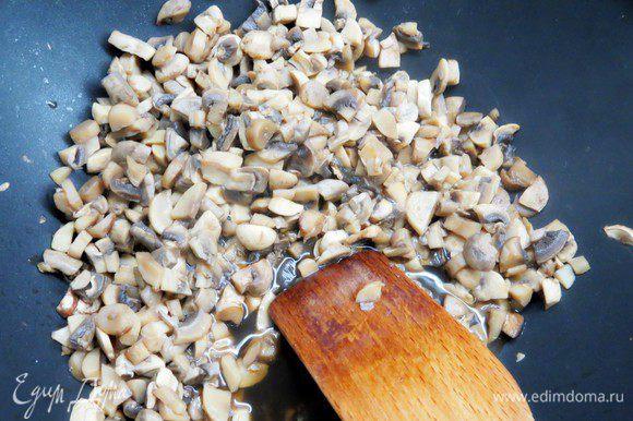 Выложить грибы на сковородку и тушить, помешивая, до испарения жидкости.