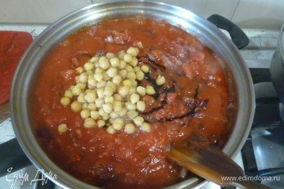 Добавить томатную пасту, томатное пюре, уксус, нут и немного кипятка. Довести до кипения, готовить на слабом огне 30 минут.