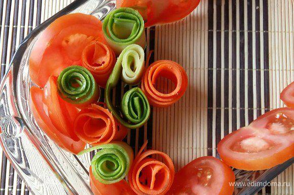 Берем блюдо (у меня прямоугольное размером 14*23). По бортикам укладываем колечки помидоров. Затем начинаем сворачивать каждую пластинку кабачка и моркови в ролл. Укладываем плотненько друг к другу в блюдо. На фото начало процесса. К сожалению, забыла сфотографировать окончание, когда были уложены все роллы, но поверьте на слово, смотрится очень красочно. Также можно проявить фантазию и добавить еще какой-нибудь овощ, цвет которого отличается от этих цветов. Например, баклажан.