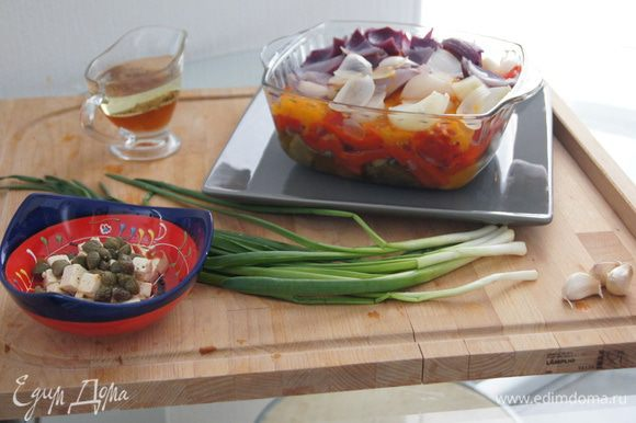 Готовим заправку. Соединяем 5 столовых ложек оливкового масла, 1 столовую ложку белого винного уксуса, соль, перец. Нарезаем мелко пучок зеленого лука. Добавляем фету и каперсы.
