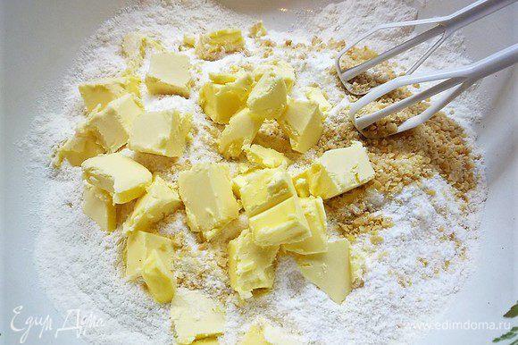 Приготовим тесто сабле. В чашке смешиваем муку, сахарную пудру, молотый миндаль. Добавляем нарезанное кусочками сливочное масло и все перетираем в крошку.