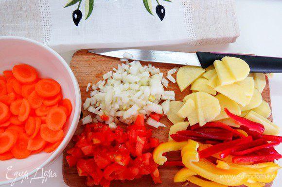 Режем овощи. Лук — кубиками, морковь — тоненькими кружочками, картофель — кружочками потолще, перец — соломкой, помидоры — кубиками.