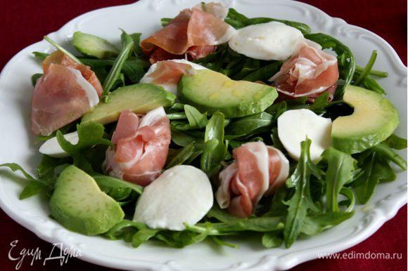 Сверху на руколу поместить моцареллу, ветчину, ломтики авокадо. Полить оливковым маслом, приправить солью и перцем .
