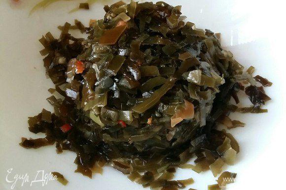 Из банки с морской капустой сливаем всю воду и перекладываем капусту в салатник.