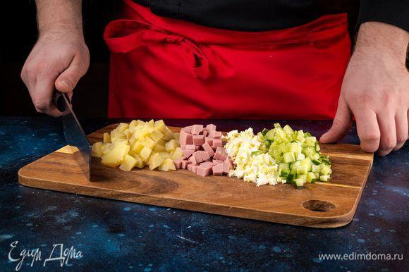 Нарежьте кубиками колбасу, очищенный картофель, очищенные яйца и огурцы.