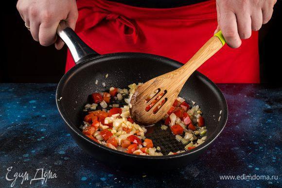 Обжарьте на сковороде в растительном масле чеснок в течение 1 минуты, добавьте лук и перец, пассеруйте 10 минут, постоянно помешивая овощи.