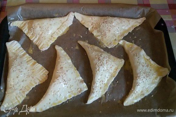 Далее формируем треугольнички и хорошо слепляем края, чтобы сыр не вытек во время приготовления. В разогретую духовку до 180°С на 15-20 минут ставим противень с нашими треугольничками, которые я уже смазала взбитым яйцом и посыпала семенами кунжута.