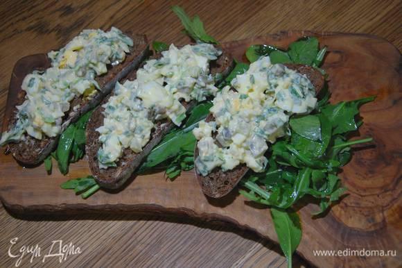 Руколу и шпинат посолить, полить оставшимся оливковым маслом и лимонным соком, перемешать и выложить на тарелку или деревянную доску, сверху поместить бутерброды с салатом.