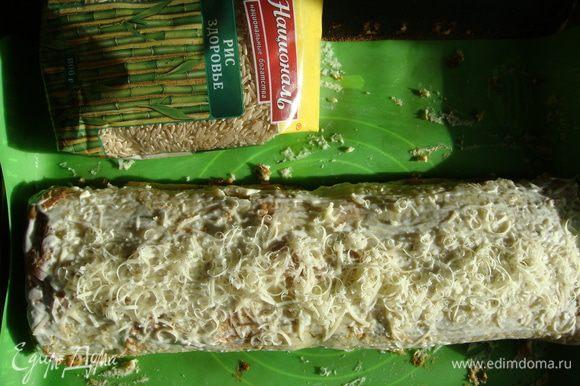 Рулет сверху смазать майонезом и посыпать натертым сыром. Переложить рулет вместе с силиконовым ковриком на противень и поставить в разогретую до 200°С духовку на 10 минут.