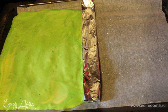 Противень застелить пергаментом, смазать 1 ч. л. растительного масла. Посередине противня положить фольгу, сложенную в два раза. На одну сторону выложить зеленое тесто, разровнять его.