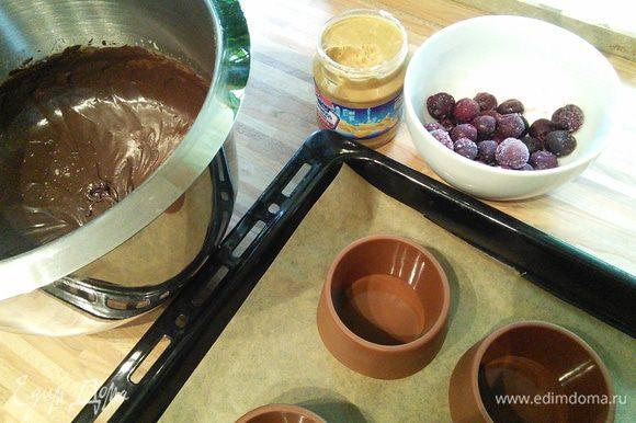 В конце аккуратно по стенке тонкой струйкой, не прекращая взбивать, влить растопленное сливочное масло. Тесто готово. Приготовить ягоду. Я заменила малину на вишню, использовала сразу замороженную. Ореховую пасту можно брать любую, главное, чтобы она была густой. Чем гуще паста, тем лучше она будет держаться в десерте. Формочки необходимо смазать маслом и посыпать мукой. У меня силиконовые, поэтому я их не смазывала.
