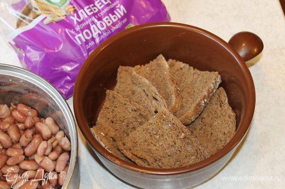 Пока жарится лук, возьмите невысокую глиняную кастрюлю. На дно кастрюли разложите ломтики тонко нарезанного хлеба. Подойдет любой серый хлеб.