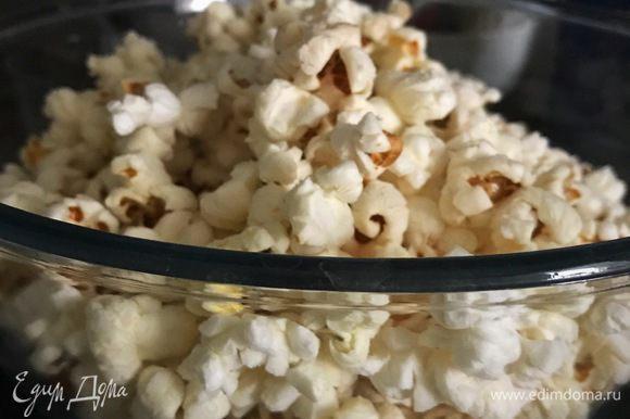 Когда стук прекратится, немедленно пересыпать попкорн в глубокую чашу. И пока зерна теплые, добавлять постепенно соль и сахарную пудру через сито, постоянно перемешивая.