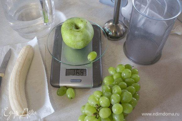 Подготовить фрукты: очистить банан, яблоко, удалить его сердцевину. Порезать фрукты на кусочки, положить в высокую емкость. Добавить горсть винограда и 50 мл воды. Взбить блендером до однородной массы.