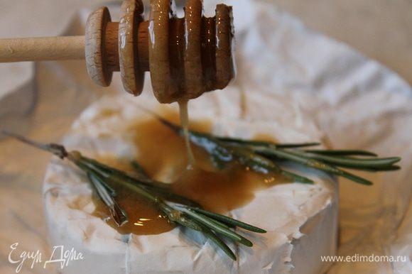 Сыр обильно полейте медом, разложите сверху веточки розмарина и отправьте его на гриль запекаться. Нарежьте багет и положите рядом с сыром, пусть немного зарумянится.