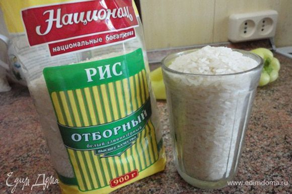 Рис ТМ «Националь» (стакан объемом 250 мл вмещает 200 г риса) промыть и отварить в воде в соотношении 1:6. На это уйдет примерно 20 минут. За это время можно подготовить овощи для запеканки.