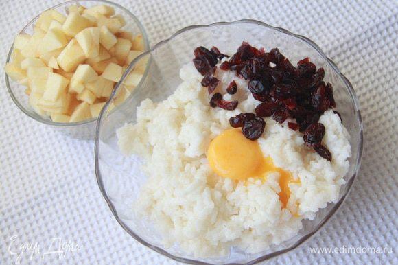 Яблоко очистить от кожуры, нарезать кубиком. В рис добавить желток, клюкву вместе в коньяком.