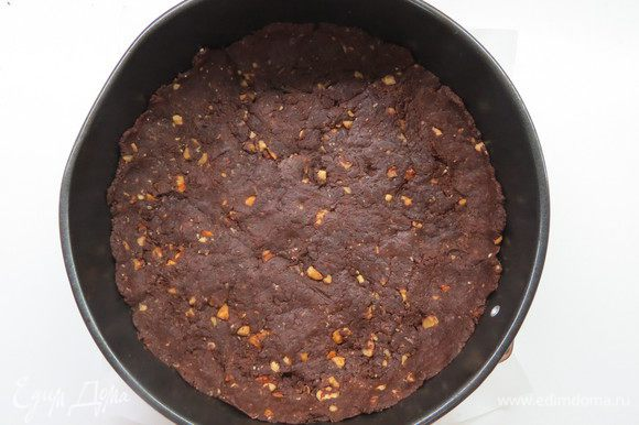 Через полчаса форму (20-22 см) проложить пергаментной бумагой, выложить тесто на дно формы для запекания. Бортики делать не надо.