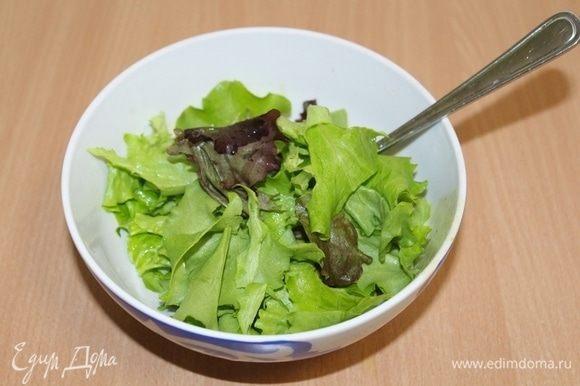 Листья салата порвать руками, полить частью заправки.