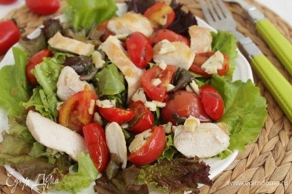 Выложить салат и помидоры на тарелку, добавить кусочки курицы-гриль, полить оставшимся соусом, добавить кусочки сыра.