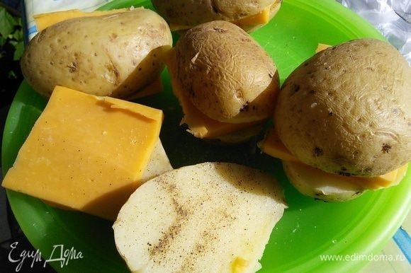 Вареный и остывший картофель разрезать на половинки. Посолить (с учетом солености сыра и бекона) и поперчить. Проложить пластинками сыра. Сыр выбирайте на ваш вкус, пластинки желательно брать потолще.