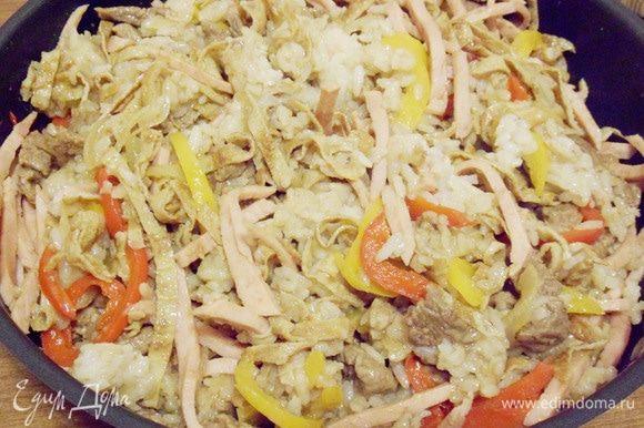 В сковороду к луку с перцем выложить рис, обжаренную говядину, ветчину и полоски омлета. Влить оставшийся соевый соус и приправить острым красным перцем. Все тщательно перемешать и прогреть на огне около двух минут. При необходимости добавить соль (я не добавляла).