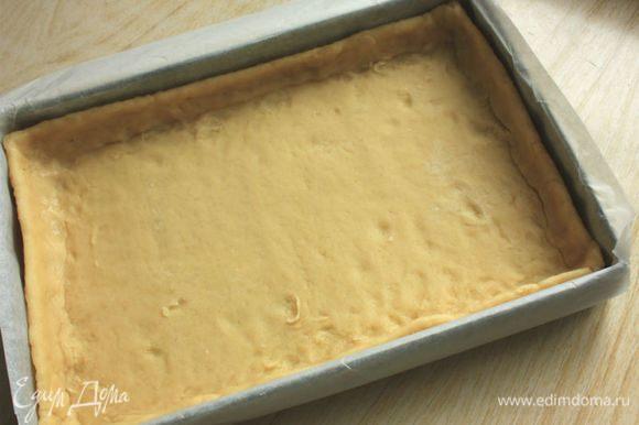 Разъемную форму для тарта (11х35 см) смазать жиром. На посыпанной мукой поверхности раскатать тесто в прямоугольник 13х37 см и перенести его в форму, прижать к стенкам. (У меня в этот момент не было под рукой разъемной формы, поэтому я застелила противень пергаментом, чтобы можно было легко вынуть базу для тарта.) Излишки теста обрезать, дно наколоть вилкой.