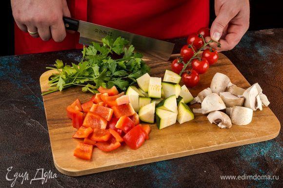 Подготовьте овощи и грибы. Шампиньоны разрежьте на части, болгарский перец и цуккини нарежьте кусочками, помидоры черри оставьте целыми.