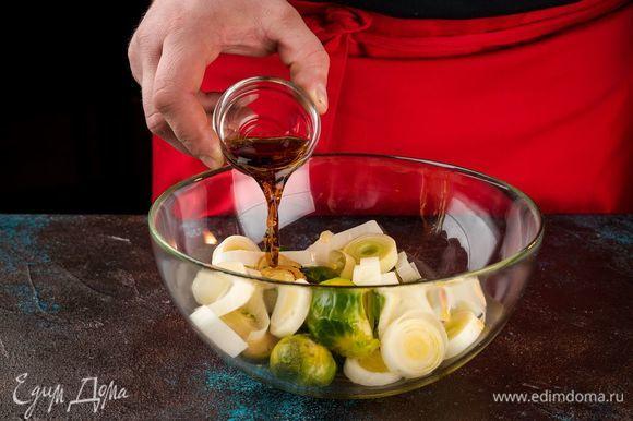 Смешайте капусту, лук, чеснок, оливковое масло, уксус. Посолите по вкусу. Выложите в форму для запекания. Запекайте в духовке 25 минут при 180°С.