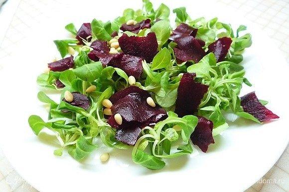Выкладываем на большой тарелке горку из салата корн, на салат выкладываем ломтики свеклы, посыпаем сверху кедровыми орешками.