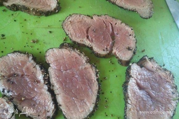Дать мясу отдохнуть 5 минут, чтобы сок распределился по куску и тонко-тонко нарезать (примерно 3 мм). Если нет острого ножа, то можно плотно завернуть кусок в пищевую пленку в несколько слоев и резать мясо как колбасу.