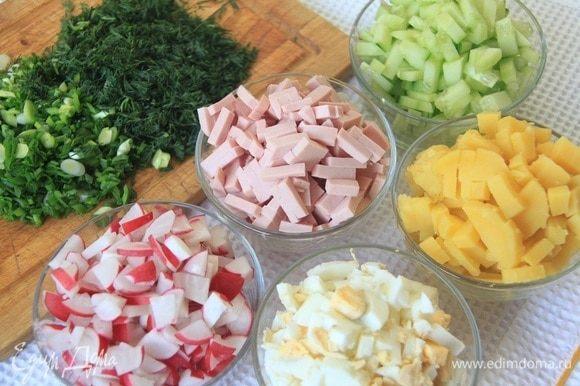 Картофель и яйца отварить до готовности, очистить и нарезать кубиком. Нарезать огурцы, редис и колбасу.