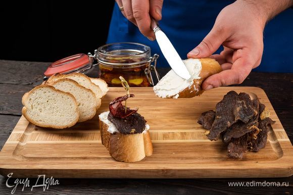 Готовим аппетитную закуску. Нарежьте хлеб небольшими кусочками, намажьте брынзу. На хлеб положите кусочек брынзы, сверху — ароматное джерки, а дальше — вяленый томат.