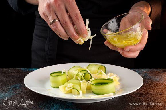 На широкую тарелку выложите картофель, сверху — огурцы, маринованный лук.