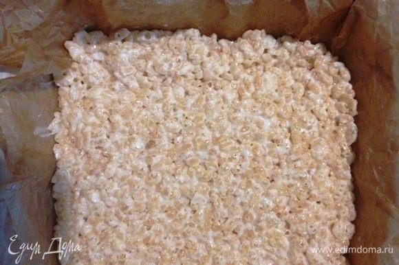 Форму для выпечки выстелить пергаментом или фольгой. Выложить готовую смесь и утрамбовать. Руки предварительно смазать сливочным маслом.