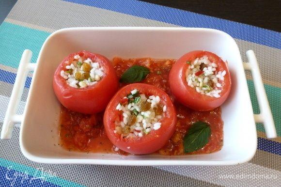 Выложим фаршированные помидоры в форму, пригодную для духовки. Зальем приготовленным томатным соком, сбрызнем оливковым маслом. Отправим в духовку на 40 минут при температуре 180°С.