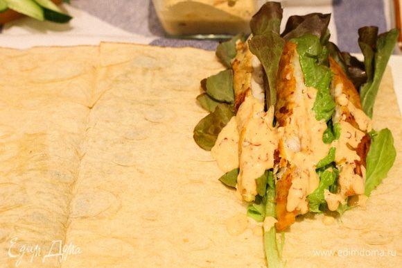На край лаваша складываем салатный лист, рыбу, поливаем все соусом и сверху складываем нарезанные овощи.