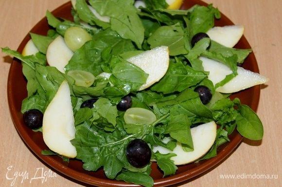 Выложить руколу, виноград без косточек, дольки груши на тарелку.
