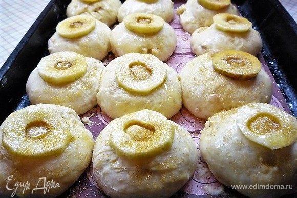 Булочки увеличились в объеме. Верх каждой булочки слегка смачиваем водой, кладем слайс яблока, сверху смазываем растопленным сливочным маслом и посыпаем коричневым сахаром.