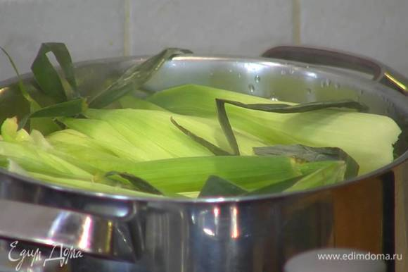 В большой кастрюле вскипятить воду, поместить в нее кукурузу, так чтобы она была покрыта водой, сверху разложить кукурузные листья, накрыть крышкой и варить 20 минут.