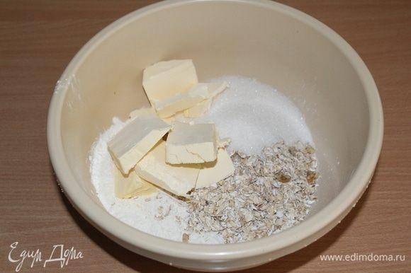 В миске соединить муку, овсяные хлопья, сахар и холодные кусочки сливочного масла. Измельчить все руками в крошку.
