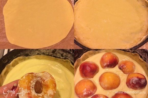 Тесто разделить на 2 части. Раскатать одну часть теста (я это делаю на присыпанном мукой пергаменте), перенести тесто в форму и распределить. Сверху тесто полить кремом, в каждый персик положить миндаль и выложить сверху на крем.