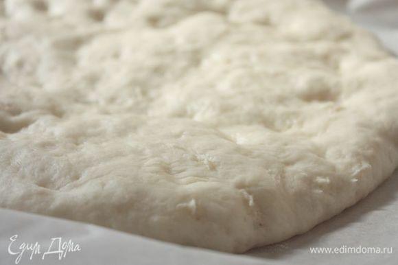 Подошедшее тесто выложите на теплый противень, застеленный бумагой для выпечки, накройте полотенцем и снова оставьте на 20-30 минут.