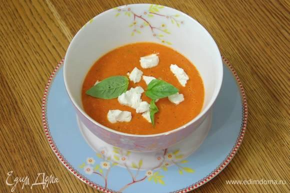 Разлить суп в тарелки, сверху разложить разломленный на кусочки козий сыр, украсить листьями базилика.