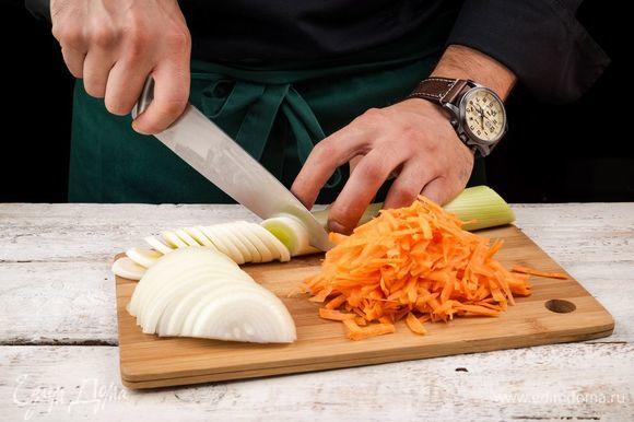 Нарежьте полукольцами репчатый лук и белую часть лука-порея, морковь очистите и натрите на терке.