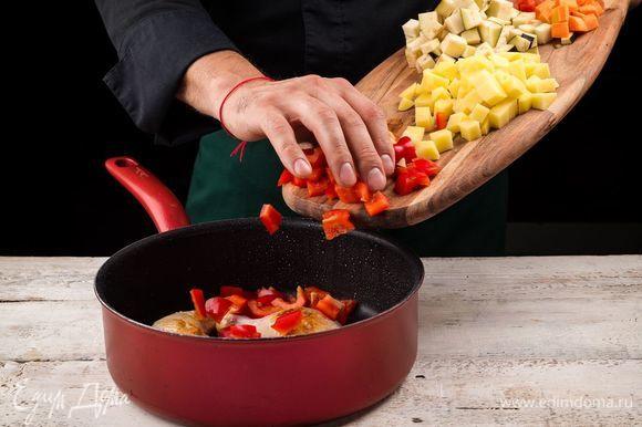 Нарежьте кубиками помидоры, болгарский перец, картофель, морковь и баклажан. Добавьте к мясу нарезанные овощи и неочищенные зубчики чеснока. Перчим и солим.