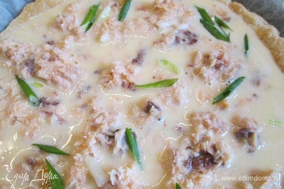 Испеченный корж достаем из духовки и заливаем яичной смесью, добавляем кусочки лосося и лук.