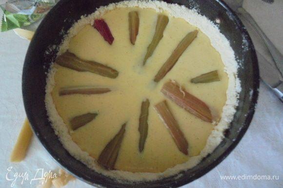 Тесто выложите в смазанную маслом круглую форму для выпекания, оформите бортики, залейте на основу ванильный крем. Сверху разложите кусочки ревеня.