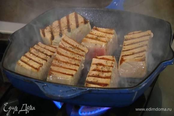 Стейки тунца посолить, поперчить, сбрызнуть оливковым маслом и обжаривать на хорошо разогретой сковороде-гриль по 3‒4 минуты с каждой стороны.
