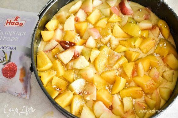В разъемную форму выкладываем тесто, выравниваем сверху персики, нарезанные кубиками. Слегка посыпаем их сахарной пудрой.